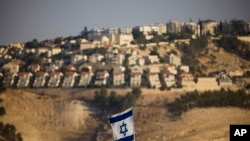 FILE - An Israeli flag is seen near the West Bank Jewish settlement of Maaleh Adumim on the outskirts of Jerusalem.