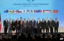 FILE - Trade delegates pose for a photograph after signing the Trans-Pacific Partnership Agreement in Auckland, New Zealand.