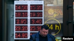 FILE - A man reads a newspaper near a currency exchange office in Kyiv, Ukraine, Nov. 10, 2014.