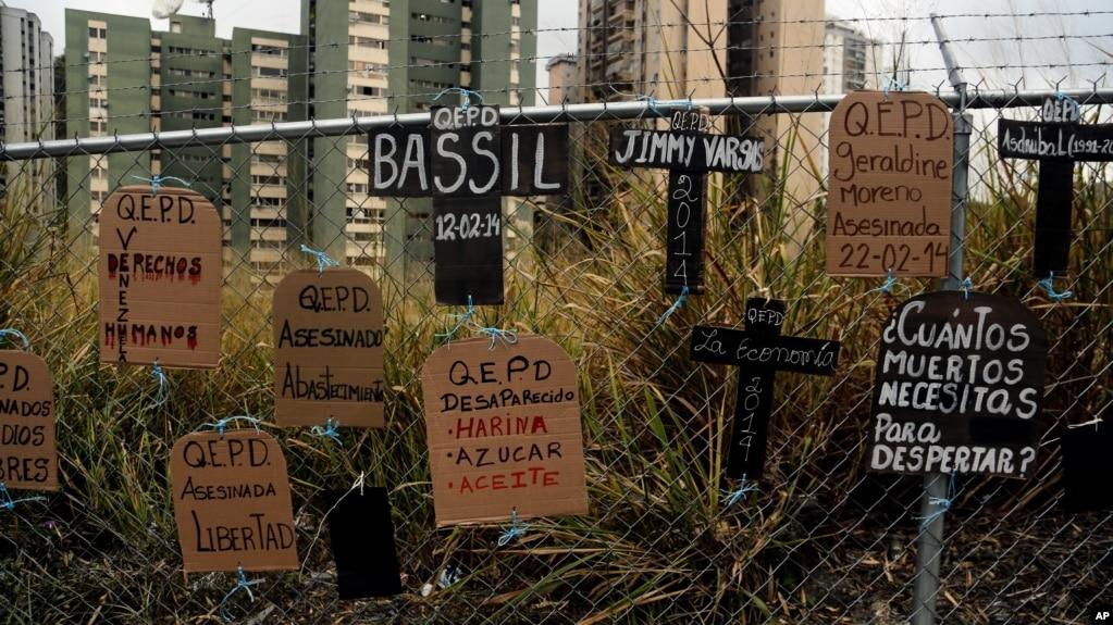 Recortes de cartón, en forma de lápidas y cruces y atados a una valla, llevan mensajes de protesta antigubernamentales y nombres de quienes murieron en protestas, en Caracas, Venezuela, el miércoles 5 de marzo de 2014.