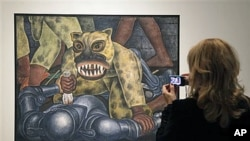 A woman looks at Mexican painter Diego Rivera's 'Indian Warrior' displayed during a preview at New York's Museum of Modern Art, November 8, 2011.