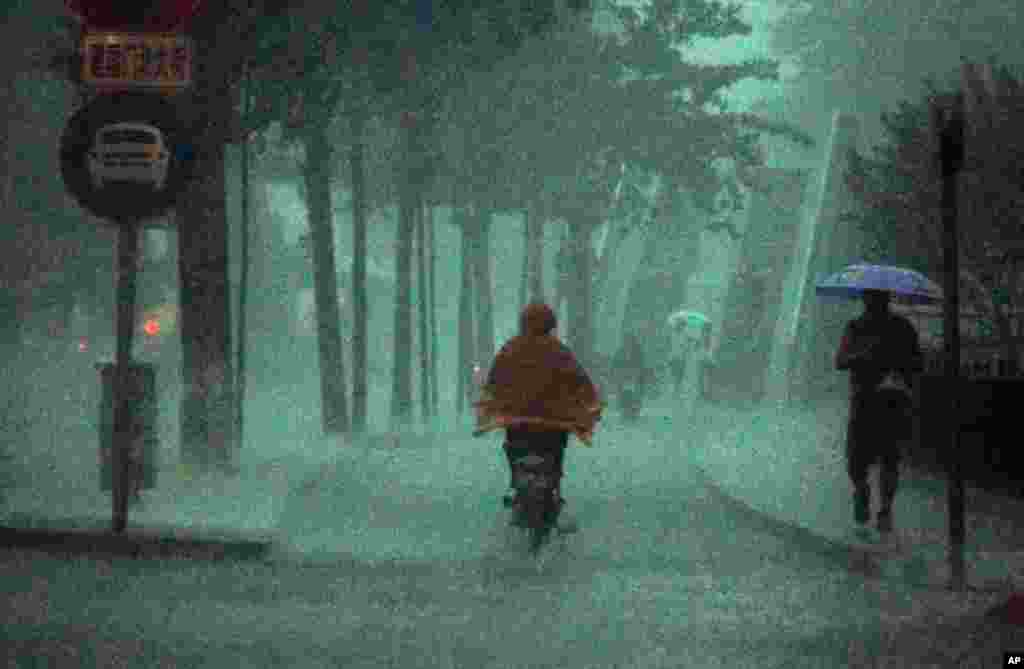 June 23: A man rides his bike during a heavy rain storm in Beijing. Torrential rains in central and southern China threaten the Yangtze River basin and nearby provinces with deadly floods and mudslides. (REUTERS/David Gray)
