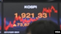 Pedagang valas tersenyum menyaksikan Indeks Harga di bursa saham Seoul, Korea (1/12).