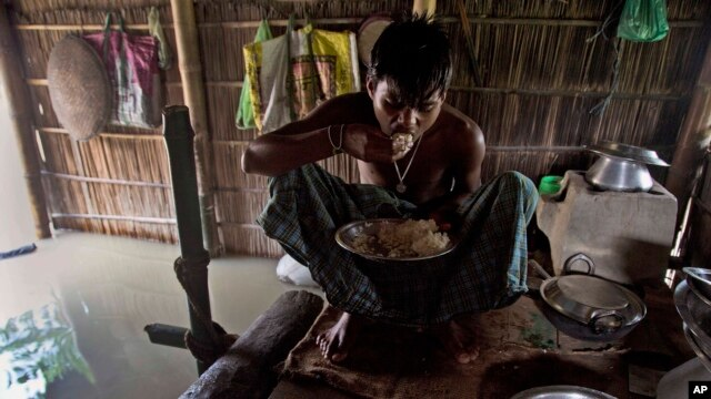 FILE - A boy eats rice inside his house in India, which is partially submerged in floodwater, Sept. 2, 2015.