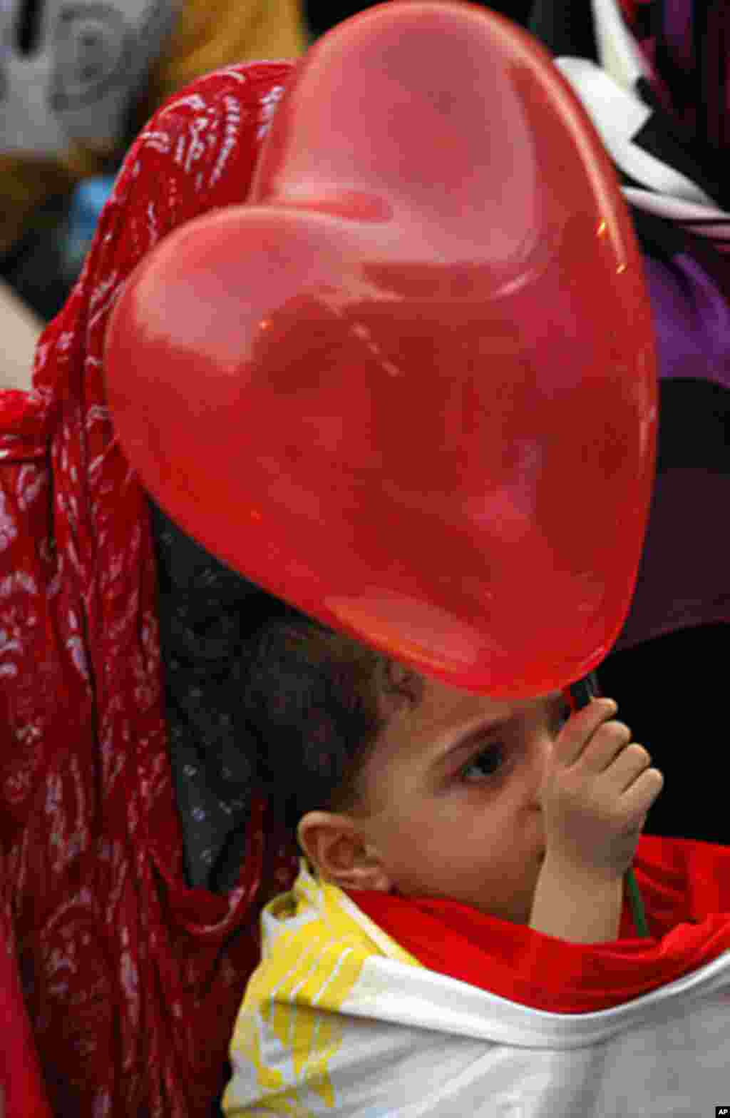 A Muslim boy holds a balloon after Eid al-Fitr prayers marking the end of Ramadan in Tahrir Square in Cairo, Egypt, Aug. 30, 2011. AP