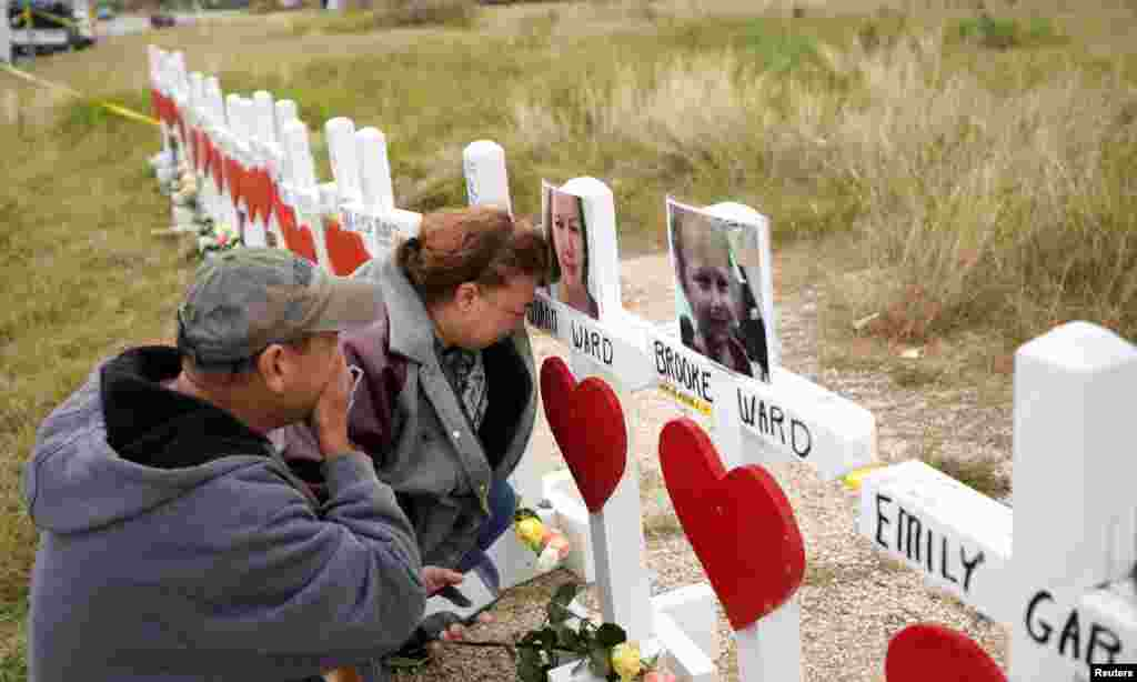 Lorenzo Flores (L) and Terrie Smith react at a line of crosses in remembrance of those killed in the shooting at the First Baptist Church of Sutherland Springs, Texas.