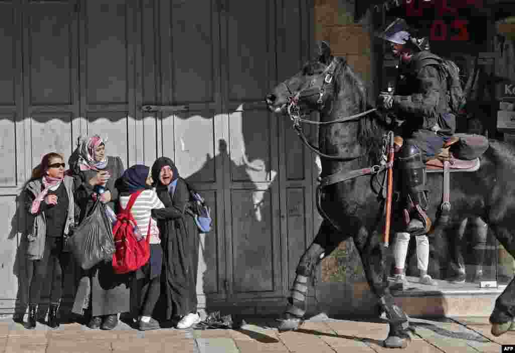 Para perempuan Palestina bereaksi ketakutan saat polisi Israel yang berkuda membubarkan demonstran Palestina di Yerusalem Timur.