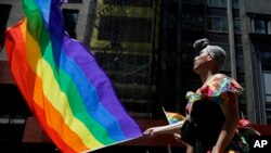 A bandeira do orgulho gay numa parada gay em Nova Iorque