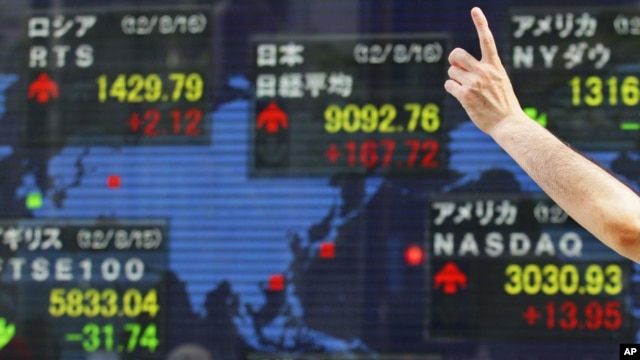 FILE - A man gestures in front of a securities firm's electronic stock board in Tokyo.
