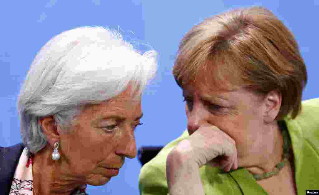 صحبت در گوشی انگلا مرکل، صدر اعظم آلمان با کریستین لاگارد، رئیس صندوق بین المللی پول در یک کنفرانس خبری در آلمان.