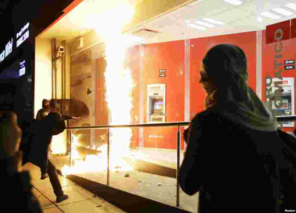 A demonstrator throws a firebomb at the windows of an ATM facility during a protest in support of the 43 missing trainee teachers in Mexico City.