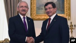 Turkish Caretaker Prime Minister and leader of the Justice and Development Party (AKP) Ahmet Davutoglu (R) shakes hands with the leader of the main opposition Republican People's Party (CHP) Kemal Kilicdaroglu, in Ankara, Turkey, Aug. 10, 2015.
