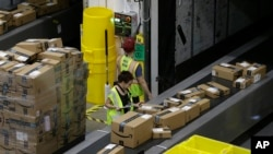 FILE - Packages move down a conveyor system were they are directed to the proper shipping area at the new Amazon Fulfillment Center, Feb. 9, 2018, in Sacramento, Calif.