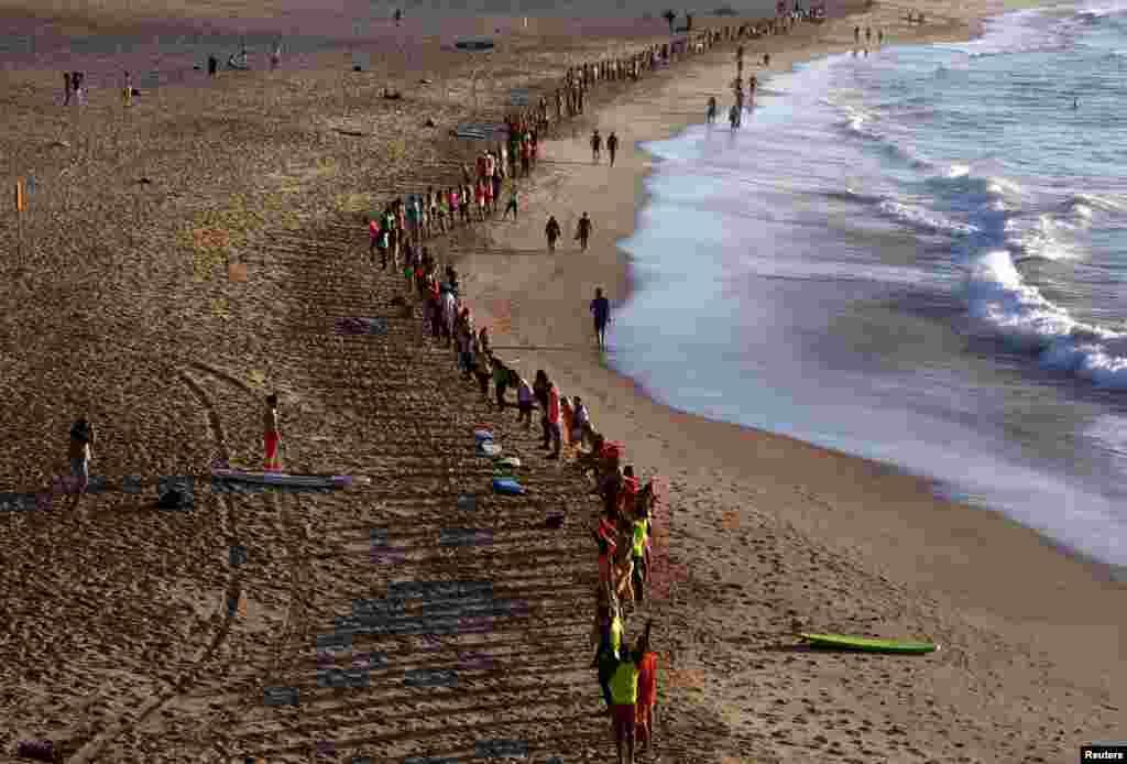 Anggota komunitas peselancar di Sydney, Australia melakukan upacara di pantaiBondi.
