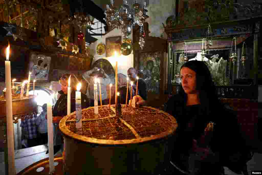 A worshiper lights candles inside the Church of Nativity, ahead of Christmas in the West Bank city of Bethlehem.