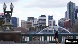 A lone woman, wearing a protective face mask, walks across an unusually quiet city centre bridge on the first day of a lockdown as the state of Victoria looks to curb the spread of a coronavirus disease (COVID-19) outbreak in Melbourne, Australia, July 16