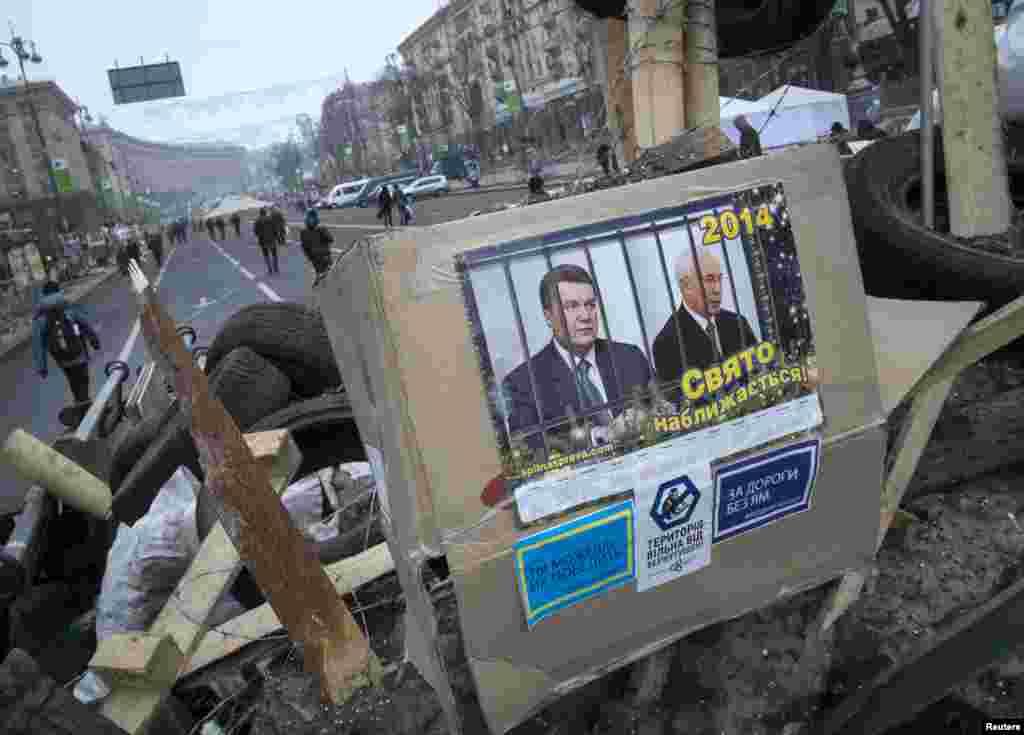 Portraits of Ukrainian President Viktor Yanukovych and Prime Minister Mykola Azarov are seen at a barricade during a rally in central Kyiv, Ukraine, Dec. 20, 2013.