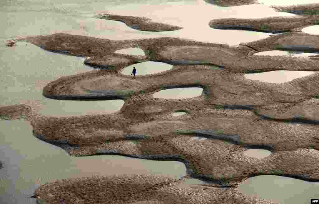 A man walks along the riverbed of the Hanjiang River during its dry season in Shiyan, central China's Hubei province, Apr. 9, 2013.