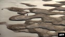 中國的乾旱正在不斷擴大。圖為一名男子在湖北漢江乾涸的河床上行走。(資料照片)