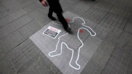 A pedestrian walks over an illustration to draw attention to domestic violence against women, on International Women's Day in central Istanbul, Turkey, in this March 8, 2013, file photo.