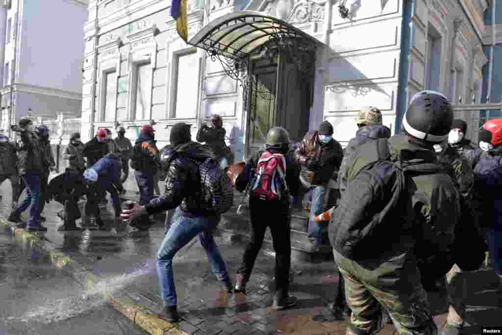 Demonstran anti-pemerintah melemparkan batu ke arah kantor partai pro-presiden di Kyiv (18/2).