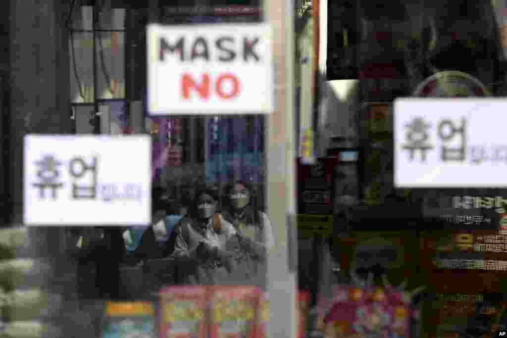 Women wearing a face mask are seen in a window of a temporarily closed store in Seoul, South Korea, March 18, 2020.