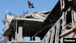 Un drapeau du groupe Etat islamique flottant au-dessus des ruines d'une maison de Raqqa, ex-capitale de l'organisation en Syrie, le 18 octobre 2017.