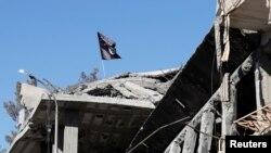 Arhiva - Zastava militanata Islamske države vijori se iznad uništene zgrade u Raki, Sirija, 18. oktobra 2917.