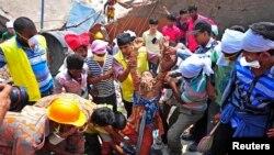 4月25日在达卡郊外,救援人员从一座坍塌的大楼的废墟中救出一名制衣厂的工人