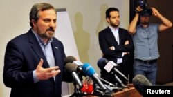 Louay al-Safi, spokesman for the Syrian National Coalition (L), speaks during a news conference in Istanbul May 26, 2013.