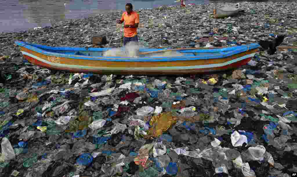 A fisherman prepares his net on the shores of the Arabian Sea, littered with plastic bags, in Mumbai, India.