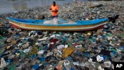 ຄົນຫາປາຜູ້ນຶ່ງ ກຳລັງກະກຽມແຫຂອງລາວ ຢູ່ທະເລອາຣັບ ທີ່ເຕັມໄປດ້ວຍຂີ້ເຫຍື້ອຖົງ plastic ທີ່ນະຄອນ Mumbai ປະເທດ India.