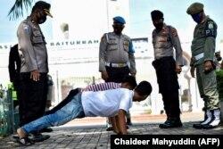Beberapa orang pria sedang melakukan push up sebagai hukuman karena tidak memakai masker di tengah pandemi Covid-19 di Banda Aceh pada 10 November 2020. (Foto: AFP/Chaideer Mahyuddin)