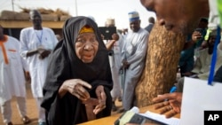 FILE - A Nigerian woman validates her voting card with a fingerprint reader so she can vote later in the day in the town of Daura, March 28, 2015.