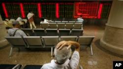 24일 중국 베이징 증권거래소에서 투자가들이 모니터를 주시하고 있다.