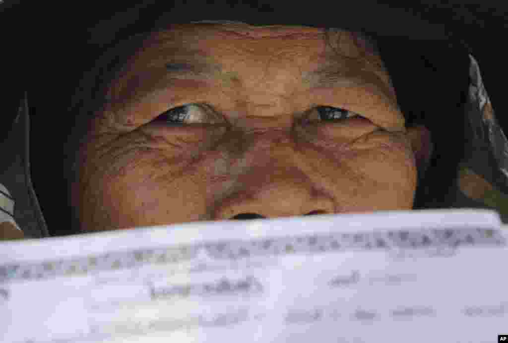A rice farmer holds her financial statements during a protest demanding payment of a rice subsidy program from the government in Bangkok, Feb. 10, 2014.