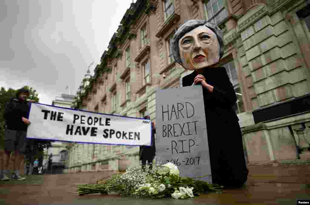 A protester wearing a Theresa May mask is seen the day after Britain's election in London.