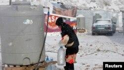 Seorang pengungsi Suriah membawa roti dan botol-botol air di tengah badai salju di kota Zahle, Lebanon (11/12). (Reuters/Mohamed Azakir)