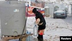 Người tị nạn Syria khiêng nước và bánh mì dưới cơn bão mùa đông ở thành phố Zahle trong thung lũng Bekaa, miền bắc Libăng, ngày 11/12/2013.
