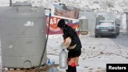 2013年12月11日,在黎巴嫩的貝卡山谷難民營的敘利亞難民在嚴冬下接水的情況。
