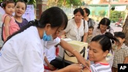 A Cambodian pregnant woman, front right, receives vaccination of A/H1N1 influenza, or swine flu, from the public health service in Phnom Penh, Cambodia, Thursday, April 1, 2010. Cambodia started its first vaccination campaign against swine flu in a series of four phases in four provinces including Cambodia's capital of Phnom Penh, said Cambodian health officers. (AP Photo/Heng Sinith)