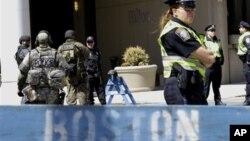 Para petugas berjaga di belakang barikade Departemen Polisi Boston dekat lokasi ledakan pada Marathon Boston, Rabu 17/4. (AP/Julio Cortez)