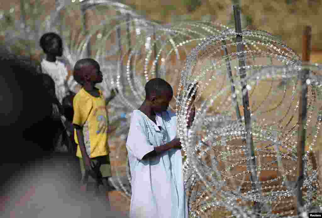 Internally displaced boys stand next to barbed wire inside a United Nation Mission in South Sudan (UNMISS) compound in Juba, Dec. 19, 2013, four days after fighting broke out in the capital city.