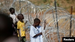 Internally displaced boys stand next to barbed wire inside a United Nations Mission in South Sudan (UNMISS) compound in Juba, Dec. 19, 2013.