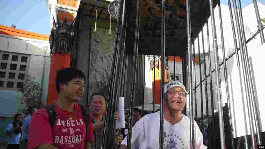 扮演王炳章的陈维明在好莱坞中国戏院前抬监游行(美国之音国符拍摄)