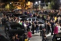Familiares y amigos se reúnen en una vigilia con cirios en el puente peatonal de Mohawk Valley Gateway en Amsterdam, N.Y., el lunes 8 de octubre de 2018. El servicio conmemoró a 20 personas que murieron en el fatal accidente de una limusina el sábado en Schoharie, N.Y.