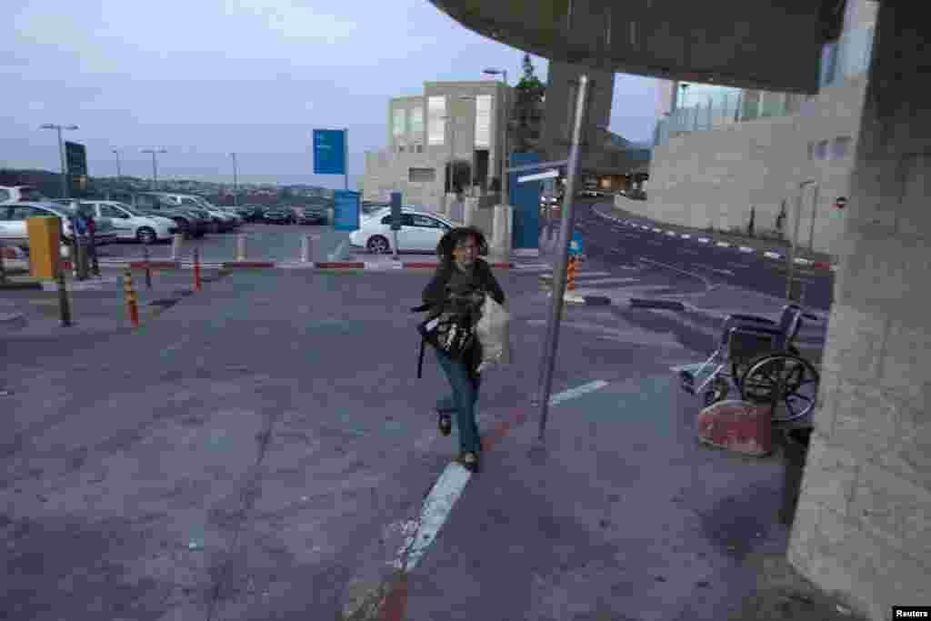 16일 이스라엘 예루살렘의 병원 주차장에서 로켓 공격 경고 알람이 울리자 급히 대피하는 여성들.