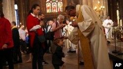Sacerdotes dan la comunión a los feligreses durante la misa del domingo de Pascua en la grandiosa iglesia Saint-Eustache en París, el domingo 21 de abril de 2019. (AP Foto/Francisco Seco)