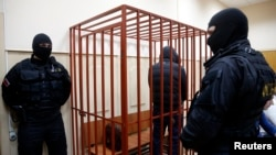 FILE - A defendant stands inside a special cage as he attends a court hearing in Sakhalin, Russia, March 4, 2015. The number of people imprisoned in Russia on extremism-related charges jumped from 137 in 2011 to 414 in 2015, according to independent research.