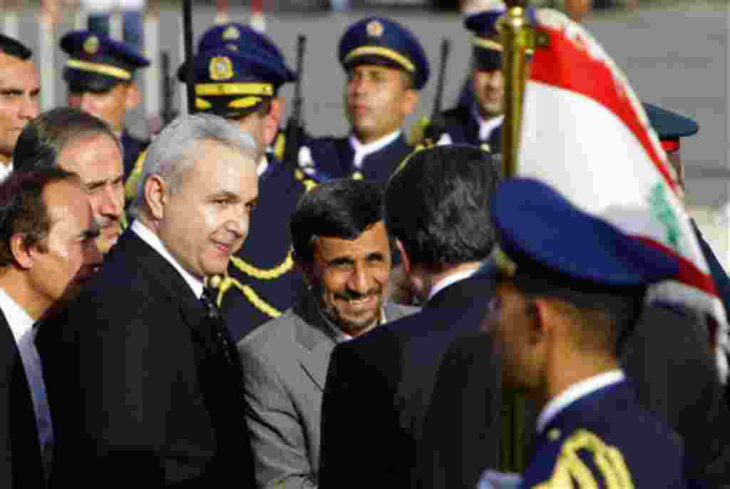 Iranian President Mahmoud Ahmadinejad, center, arrives with Lebanese Defense Minister Elias Murr, left, to lay a wreath at the Martyrs' statue in downtown Beirut, Lebanon, Wednesday, Oct. 13, 2010. Thousands of cheering Lebanese welcomed Iranian President